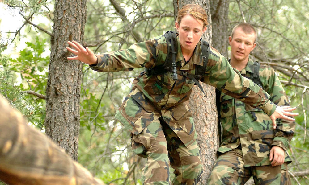 Two army people climbing trees