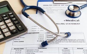 Medical billing statement, stethoscope, and calculator